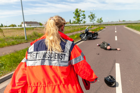 A german paramedic helps an injured motorcyclist. Rettungsdienst is the german word for ambulance service.