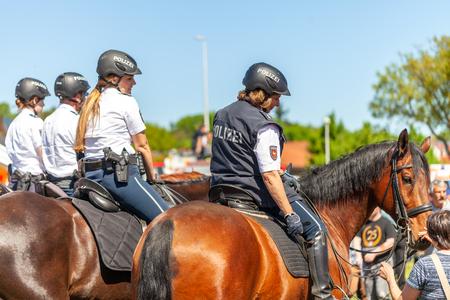 DELMENHORST/Deutschland - 6. MAI 2018: Deutsche Polizeireiterin reitet auf einem Polizeipferd zur Übung in einer Menschenmenge. Das deutsche Wort Polizei bedeutet Polizei.
