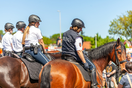 DELMENHORST / GERMANIA - 6 MAGGIO 2018: Amazzone della polizia tedesca cavalca su un cavallo della polizia per esercitazione in mezzo alla folla. La parola tedesca Polizei significa polizia.