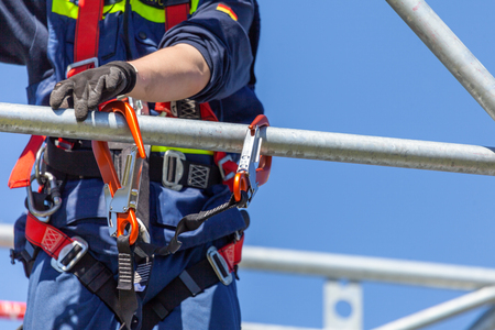 Man from german technical emergency service secured by a carabiner hook