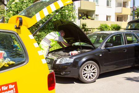 HANNOVER / GERMANY - MAY 21, 2018: Service man from ADAC, german automobile club repairs a broken car.