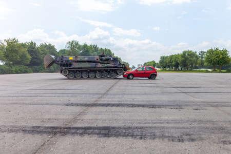 FELDKIRCHEN  GERMANY - JUNE 9, 2018: German tank dozer Dachs crashes a red car on day of the Bundeswehr in Feldkirchen.