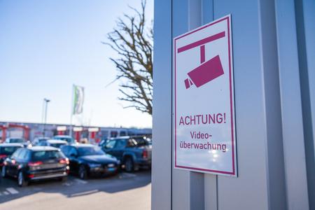 German camera sign near a parking area. Achtung, Kameraueberwachung means Caution, Camera  surveillance. 写真素材