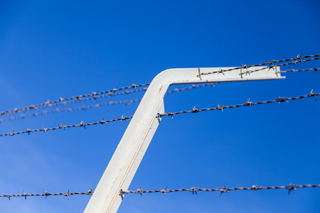 barb wire in front of blue sky