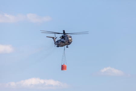 BERLIN  GERMANY - JUNE 28, 2018: Sikorsky S-65, CH-53 transport helicopter from Bundeswehr flies with a water tank in Berlin, Germany.