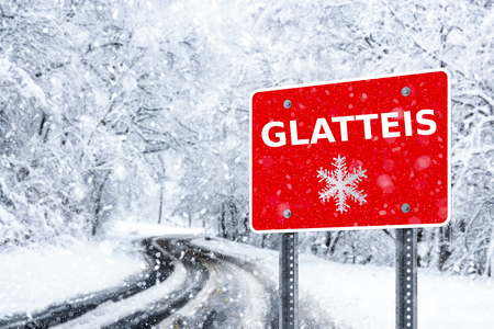 Warning traffic sign on a ice road. Glatteis is the german word for glazed frost 免版税图像