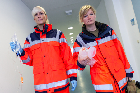 two female paramedics with emergency equipment in a floor