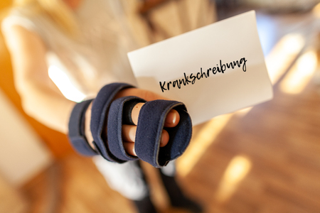 German medical certificate in a injured right hand. Krankschreibung means medical certificate