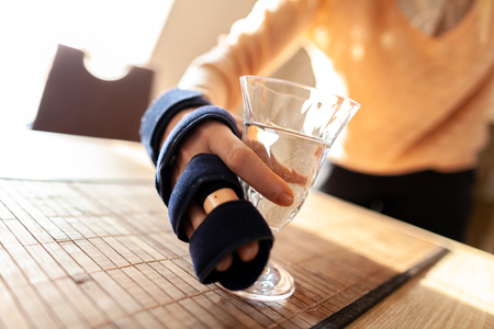 Hand holds a glass of water with a medical hand sling 写真素材