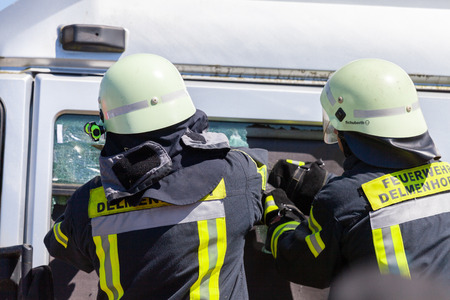 DELMENHORST  GERMANY - MAY 6, 2018: German firefighters  train on a truck accident at an open day. Feuerwehr means german fire department.