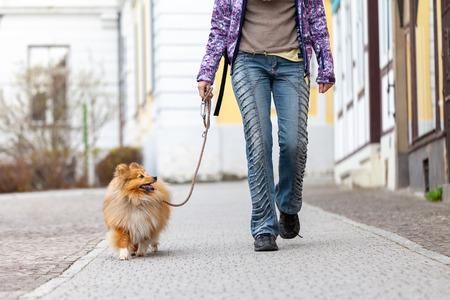 Une femme conduit son chien en laisse Banque d'images