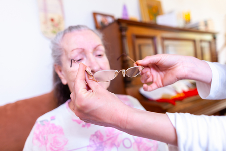 An old woman gets glasses on by a nurse