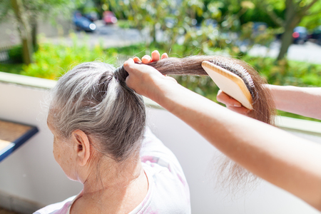 Young woman combs the hair of an old woman Reklamní fotografie
