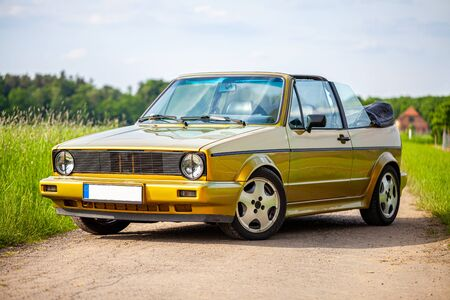 A golden german cabriolet stands on a country path