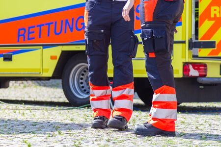 German female paramedic stands in front of an ambulance car. Rettungsdienst means ambulance service.