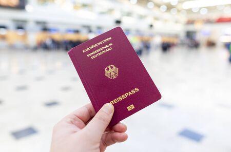 Ręka trzyma niemiecki paszport w terminalu lotniska