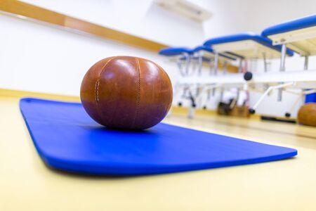 Gym ball lies on a blue sport mat
