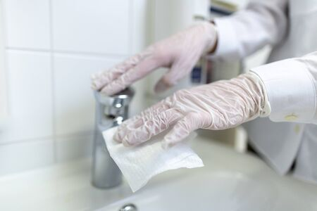 A nurse disinfects an item in a hospital room