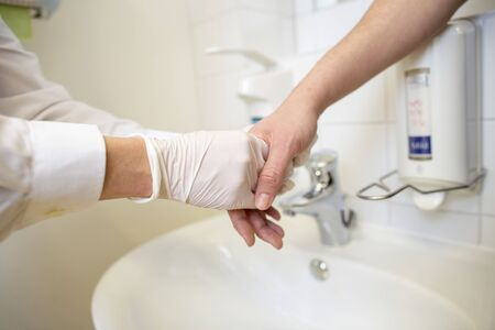 Nurse disinfects a patients hand at a sink