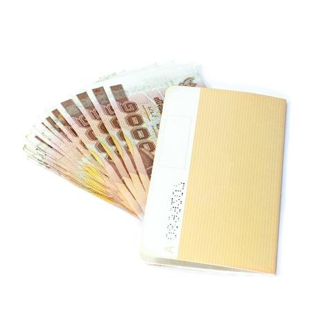 baht: Thailand passbook and Thai money on white background