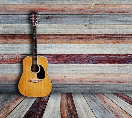 Gitaar en fotolijstje in vintage houten kamer Stockfoto