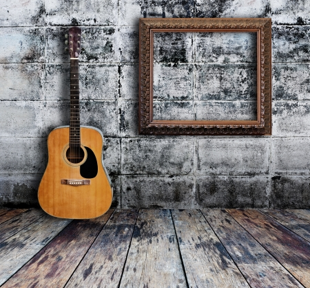 Guitar and picture frame in grunge room  Stock Photo - 15190917
