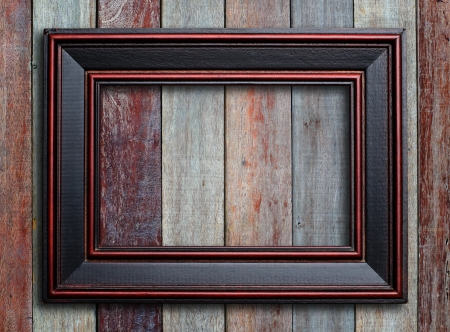 distressed wood: Old picture frame on vintage wood wall
