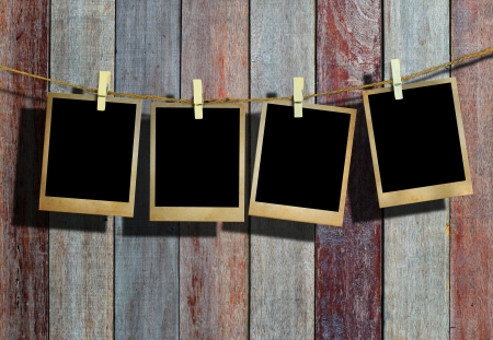 clothespin: Picture frame hanging on clothesline on wood background