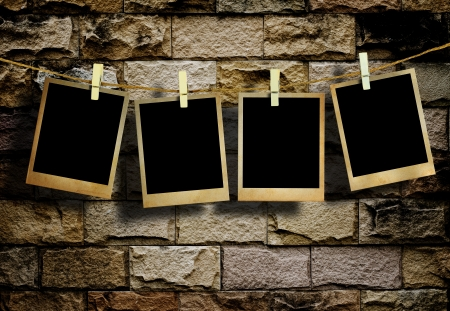 old album: Old picture frame hanging on clothesline on grunge wall