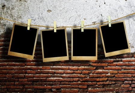 clothespin: Old picture frame hanging on clothesline on grunge wall