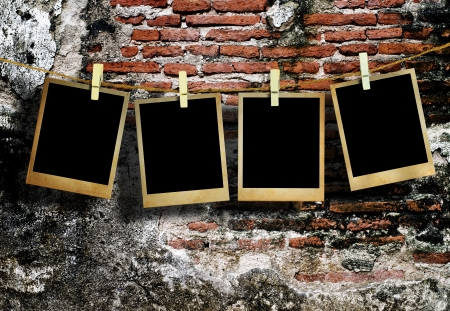 Old picture frame hanging on clothesline on grunge wall  photo