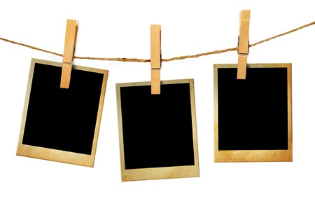 Old picture frame hanging on clothesline on wood background  photo