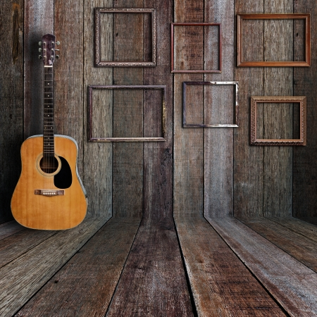 acoustic: Guitar and picture frame in vintage wood room.