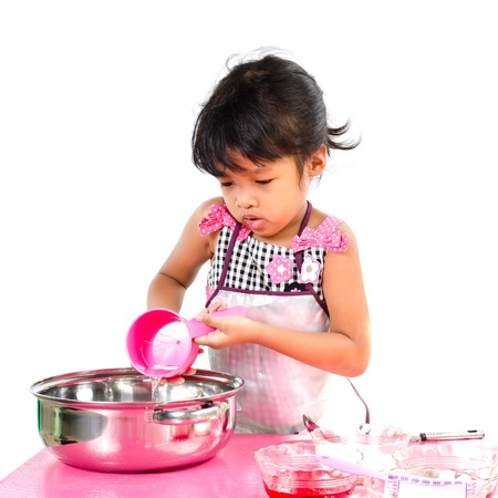Little girl cooking on white background. photo