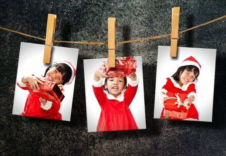 Photos of little girl wearing Santa Claus hat  hanging on grunge wall. photo