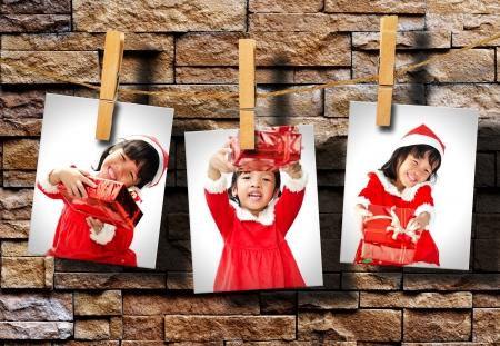 Photos of little girl wearing Santa Claus hat  hanging on grunge wall. photo
