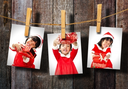 Photos of little girl wearing Santa Claus hat  hanging on wood wall. Standard-Bild
