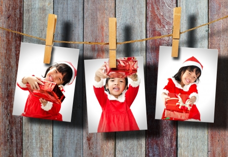 Photos of little girl wearing Santa Claus hat  hanging on wood wall. photo