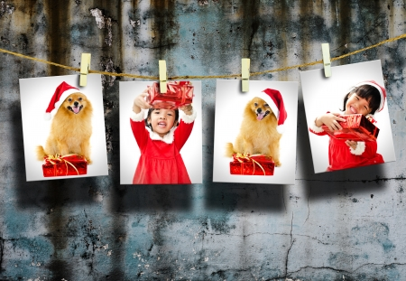Photos of little girl and dog wearing Santa Claus hat  hanging in the old room. photo