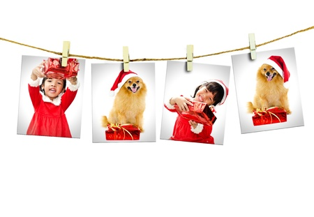 Photos of little girl and dog wearing Santa Claus hat  hanging on white background. Archivio Fotografico