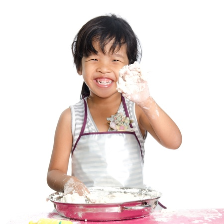 Little girl makes play dough on white background. photo