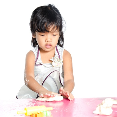 Little girl makes play dough on white background.