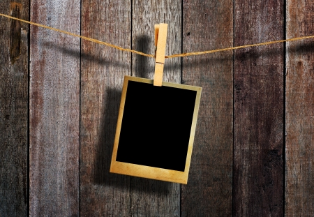 Old picture frame hanging on clothesline on grunge wall Stock Photo - 17361165