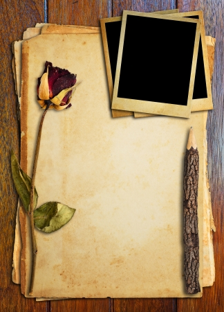 Dead roses, old pencil and old picture put on old paper. photo