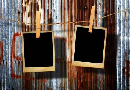 old film: Old picture frame hanging on clothesline on grunge wall.