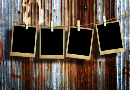 Old picture frame hanging on clothesline on grunge wall. photo