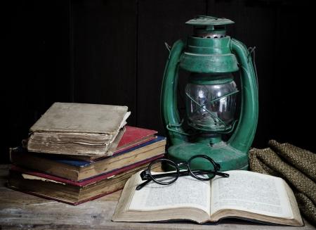 Still life with old book Kerosene lamp and glasses  Archivio Fotografico