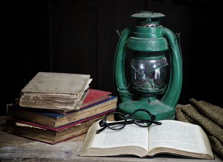 Still life with old book Kerosene lamp and glasses  Stock Photo