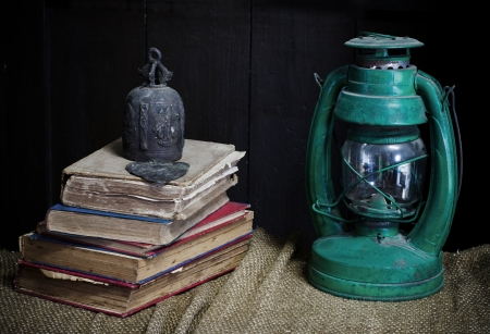 kerosene lamp: Still life with old book Kerosene lamp and old bell