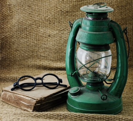kerosene lamp: Still life with old book Kerosene lamp and glasses. Stock Photo